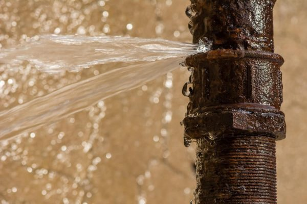 Rusty burst pipe spraying water after freezing in winter. Spring plumbing tips to avoid this happening