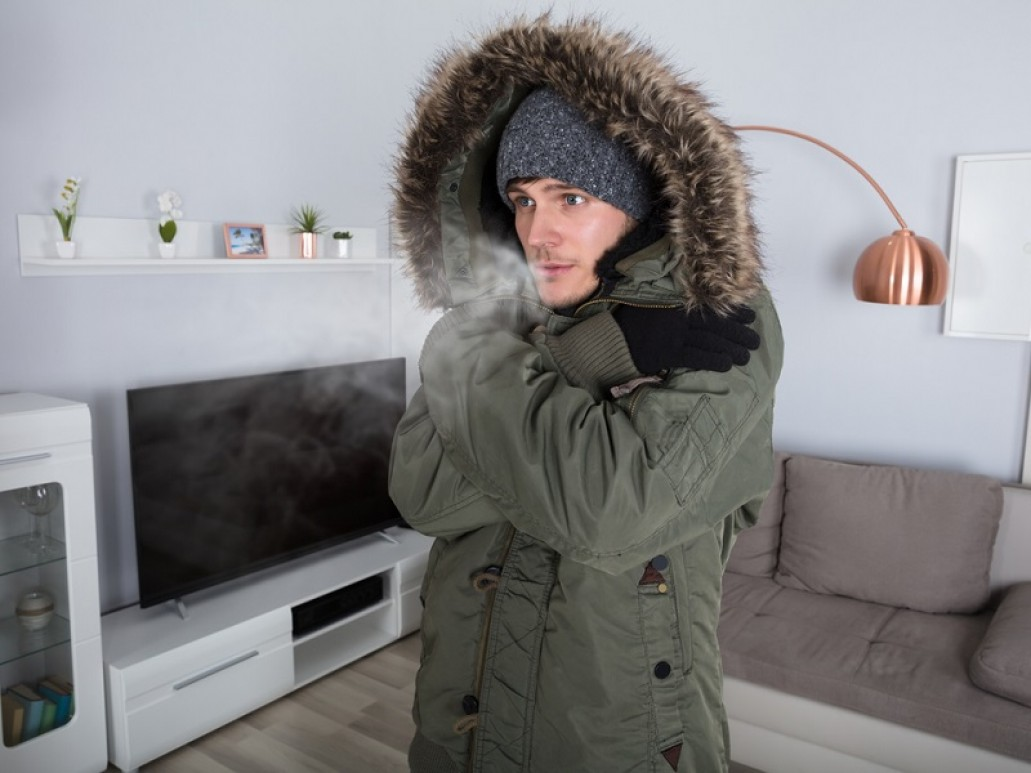 a man indoors wearing a winter coat with breath visible coming from his mouth, symbolising common central heating problems and how to fix them