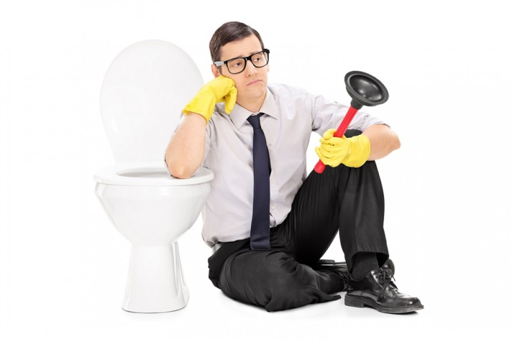 Sad man holding a plunger and sitting by a clogged toilet