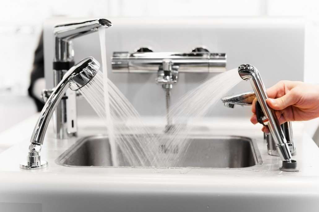 set of water mixing faucets, all turned on and wasting water.