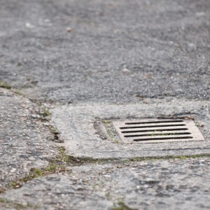 rainwater drain set in concrete surface, learn how to unblock outside drains in this blog topic
