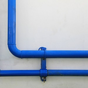 Blue pipes on a concrete wall
